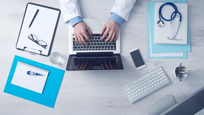 Overvioew of a desktop with an NP's hands and sleeves typing on a lap top surrounded by desk accessories and a stethescope